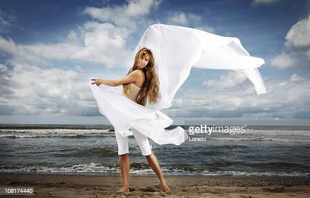 Femme sur la plage avec un tissu blanc