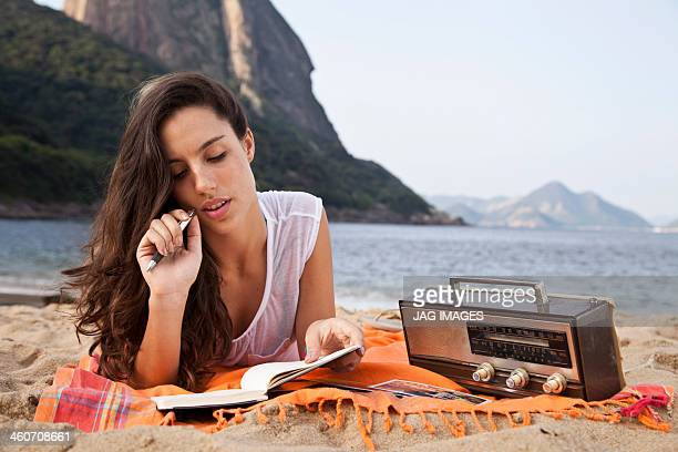 Woman on beach writing in notebook, Rio de Janeiro, Brazil