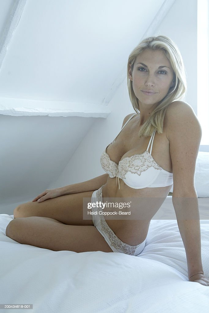 Woman on bed in lingerie smiling, portrait, close-up : Stock Photo