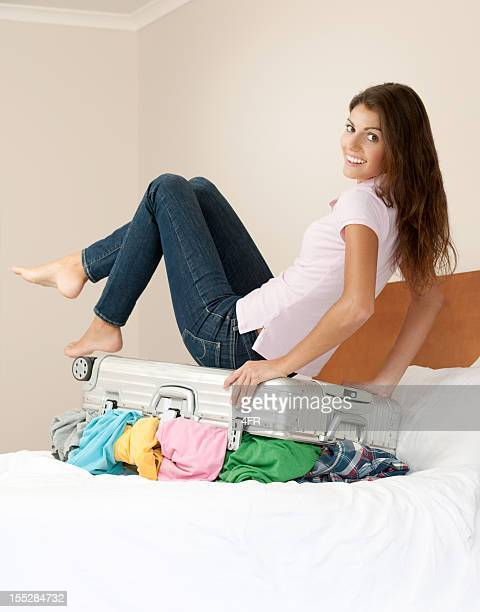 Femme sur lit de préparation de sa valise (XXXL