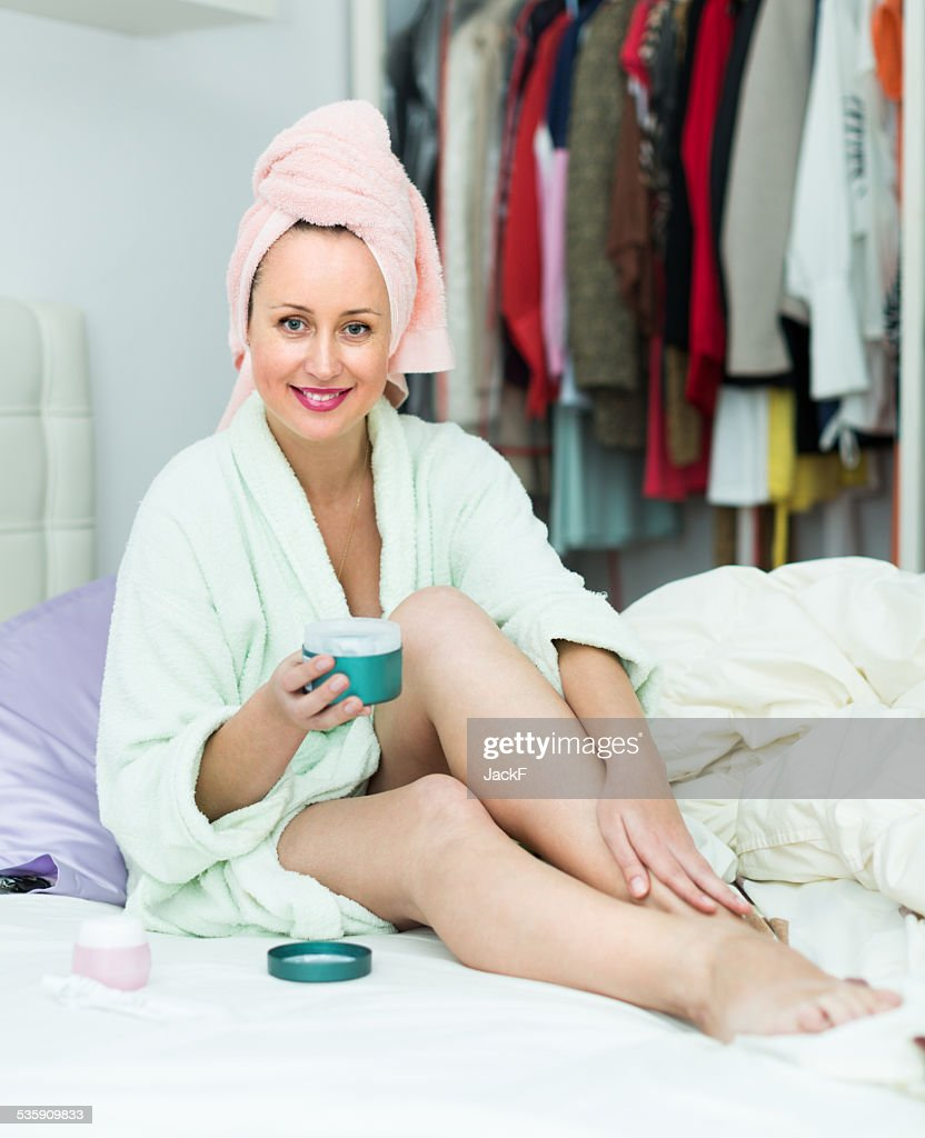 Woman on bed rubbing cream into skin : Stock Photo