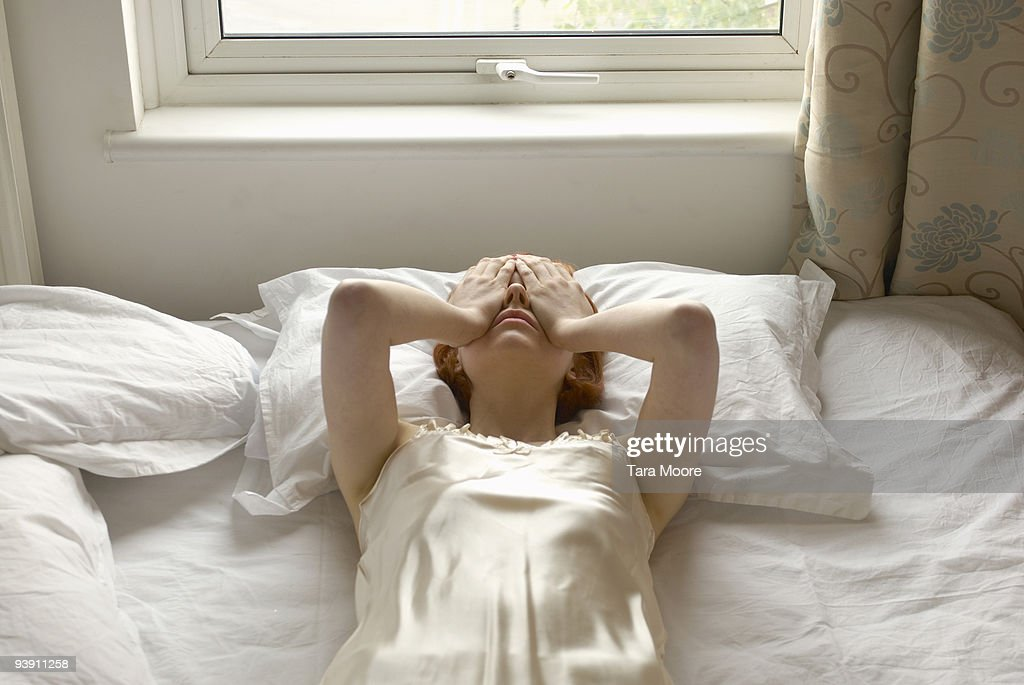woman on bed with hands over eyes : Stock Photo