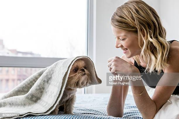 woman on bed with her pet dog under blanket