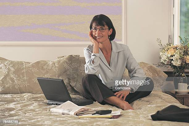 Woman on bed with laptop and cell phone