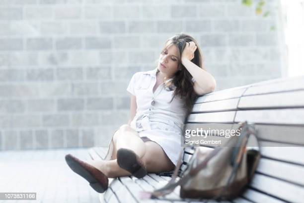 woman on bench looking tired - sigrid gombert stock pictures, royalty-free photos & images