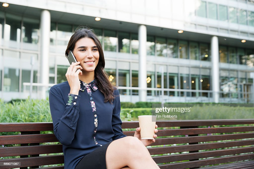 Woman on bench talking on phone : Stock Photo