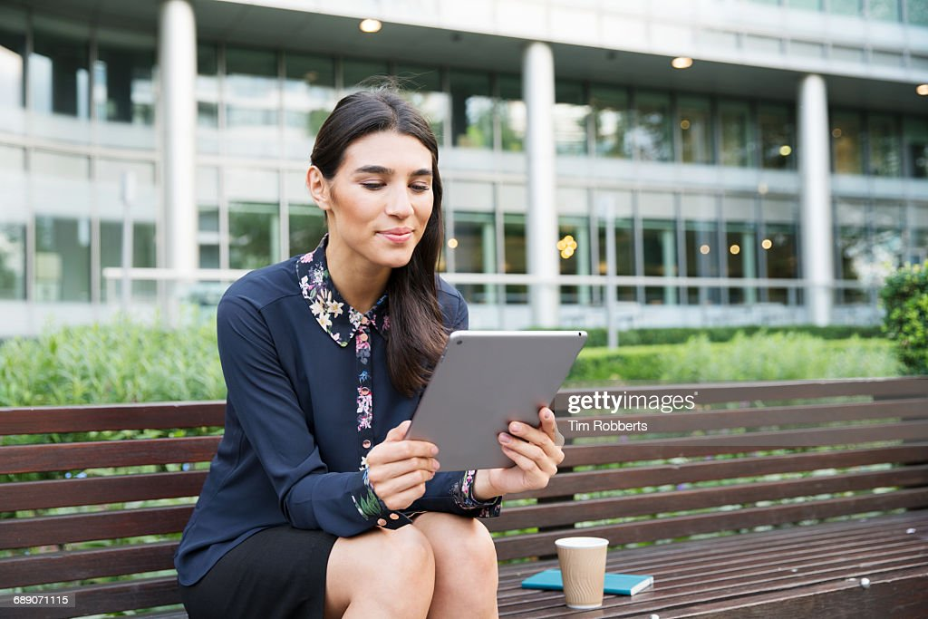 Woman on bench using tablet : Stock Photo