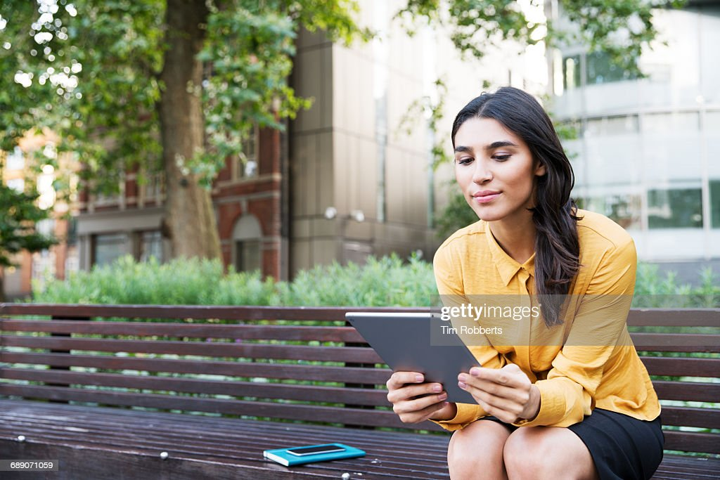 Woman on bench with tablet : Stock Photo
