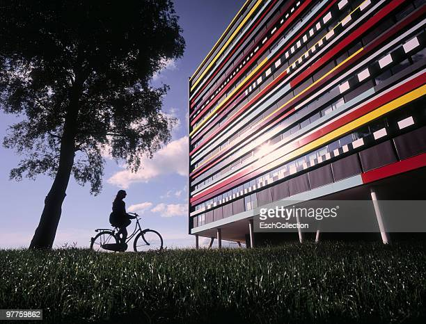 woman on bicycle arriving at colorful building. - utrecht stock-fotos und bilder