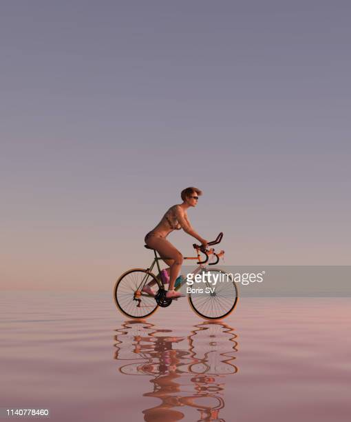 woman on bicycle riding in shallow water - cycling event stock pictures, royalty-free photos & images