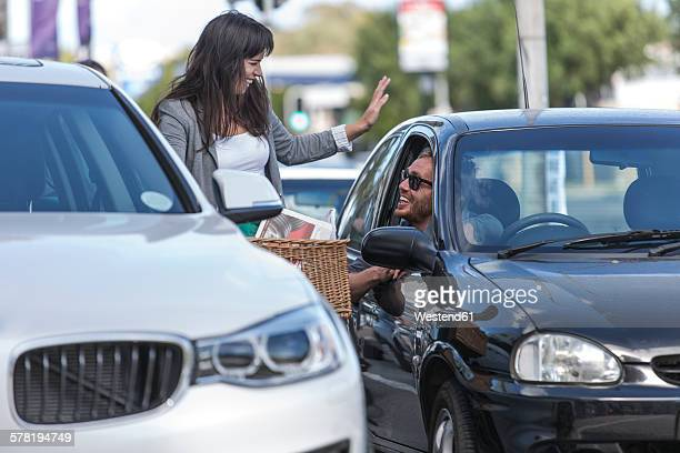 Woman on bicycle talking to man in car