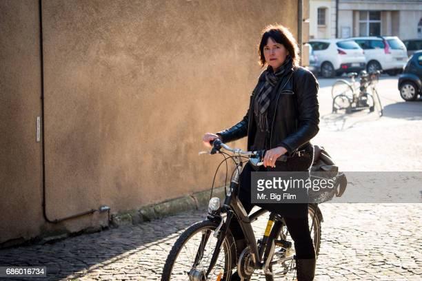 Woman on Bike On Cobblestone Street In France
