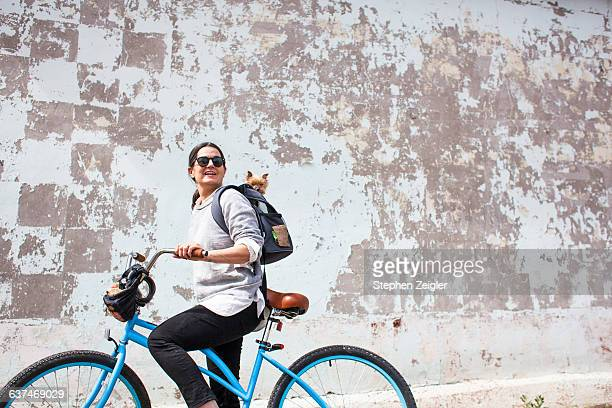 Woman on blue bike with small dog