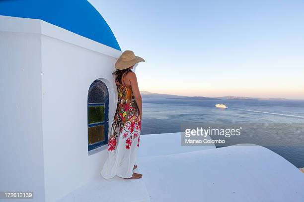 woman on blue dome church looking at cruise ship - islas griegas fotografías e imágenes de stock