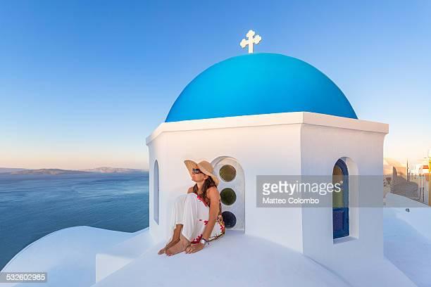 Woman on blue domed church in Santorini, Greece