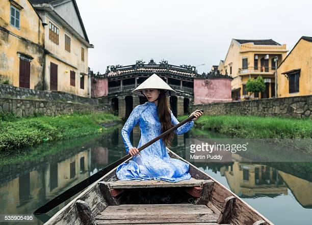 woman on boat in front of Japanese covered bridge
