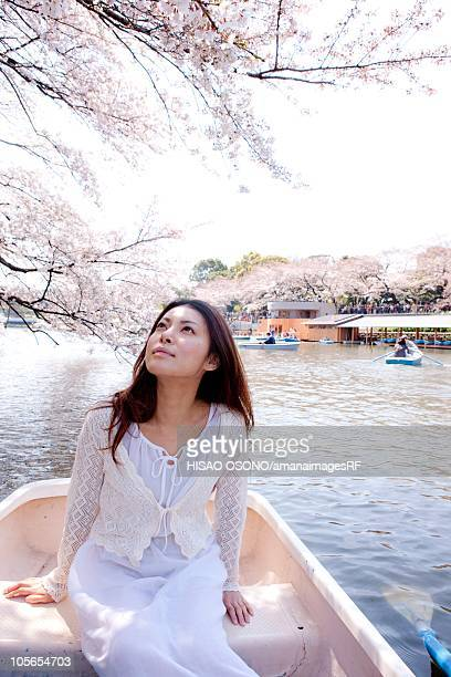 Woman on boat looking up at cherry blossoms, Tokyo Prefecture, Honshu, Japan