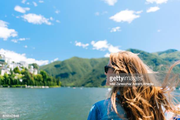 Woman on boat looks out at lake and mountains