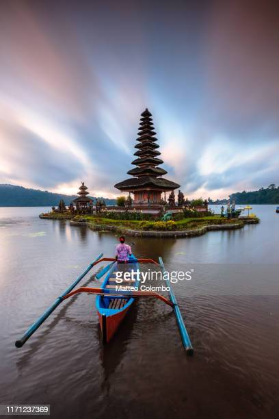 woman on boat near famous temple at sunrise, bali - lake bratan area stock pictures, royalty-free photos & images