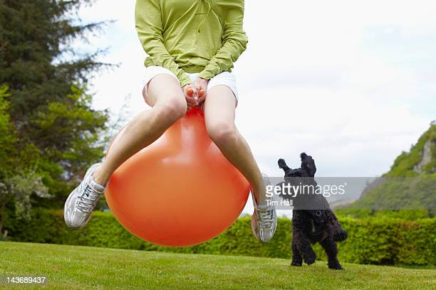 woman on bouncy ball playing with dog - bouncing ball stock photos and pictures
