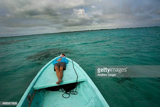 Woman on bow of boat on blue ocean.