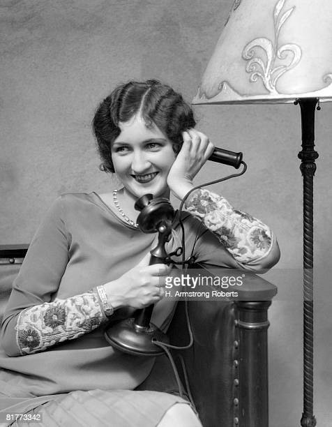 Woman On Candle Stick Phone Sitting On Couch By Lamp Smiling Flirting.