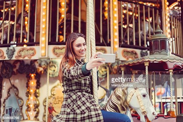 Woman on carousel ride taking selfie