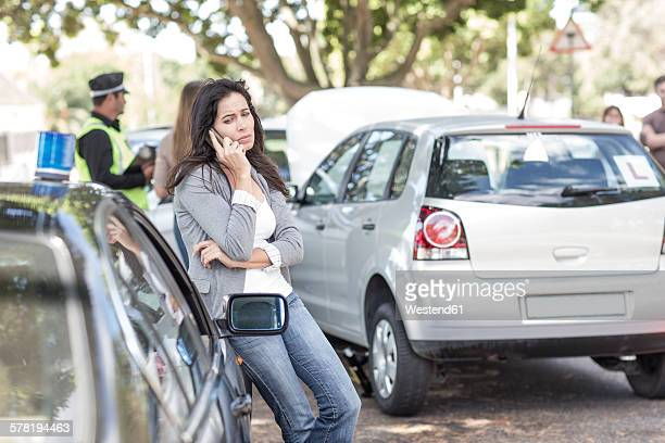 Woman on cell phone at car accident scene