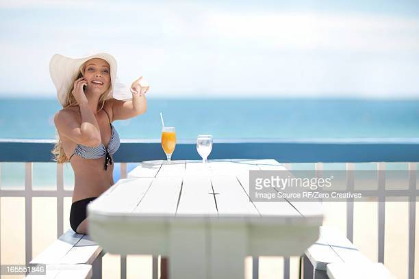 Woman on cell phone at table on deck
