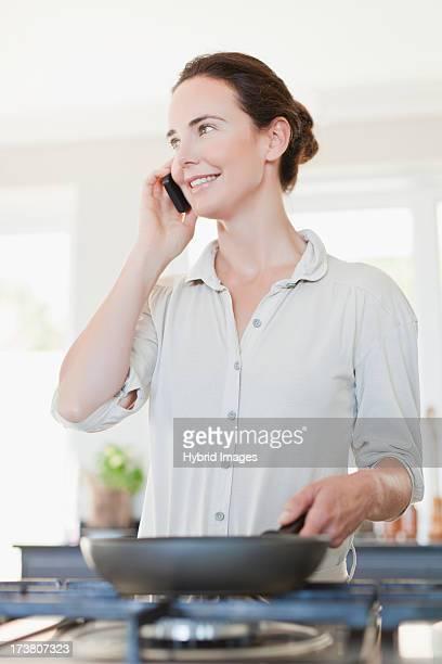 woman on cell phone cooking - rispondere foto e immagini stock