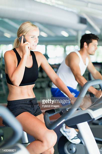 Woman on cell phone on exercise machine
