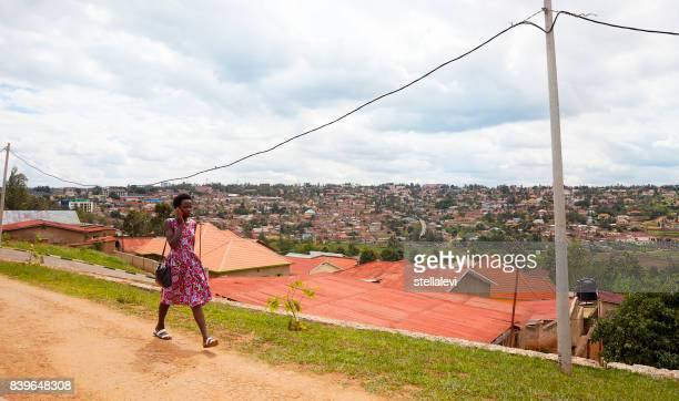 mujer en el teléfono celular al aire libre con vista de los tejados una casas. kigali. - ruanda fotografías e imágenes de stock