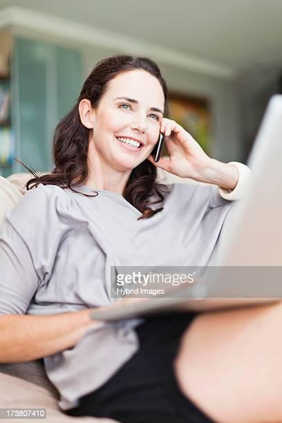 woman on cell phone using laptop - rispondere foto e immagini stock