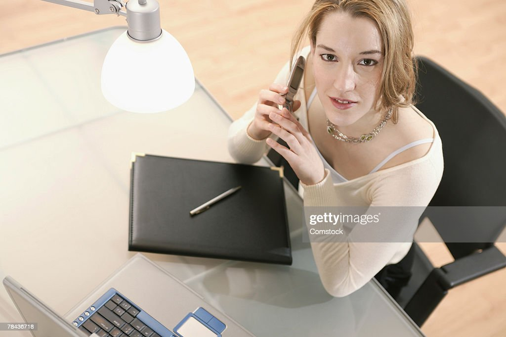 Woman on cell phone with laptop in office : Stockfoto