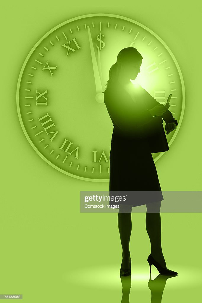 Woman on cellphone by large clock : Stockfoto