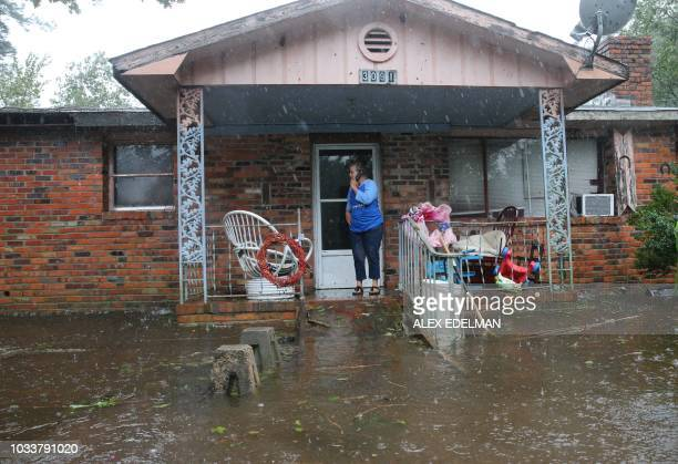 A woman on cellphone calls for help at her flooded residence in Lumberton North Carolina on September 15 2018 in the wake of Hurricane Florence...