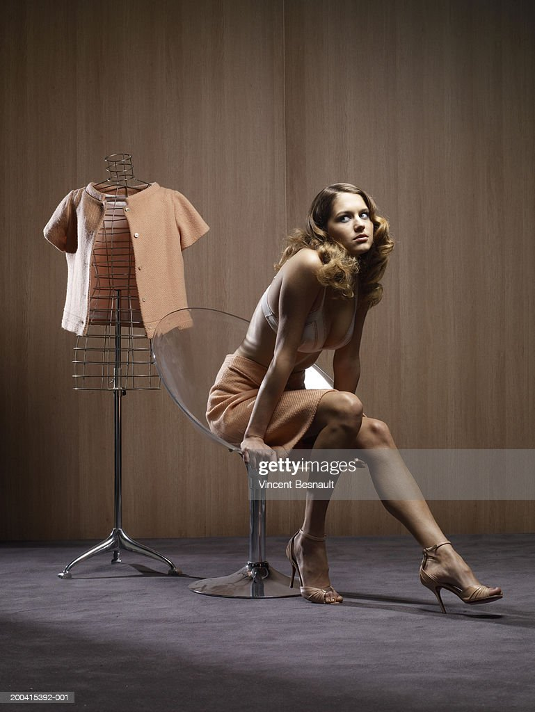 Woman on chair by jacket on dressmaker's model : Stock Photo