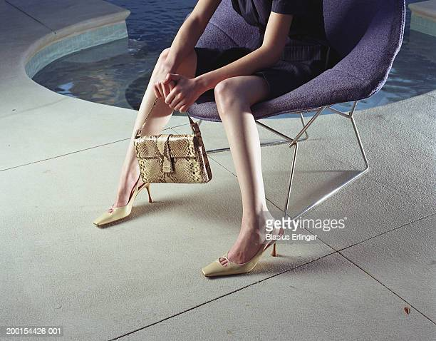 Woman on chair holding handbag near pool