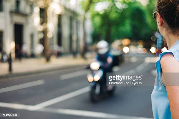 woman on city street by building - moped stock photos and pictures