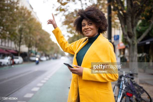 woman on city street hailing a taxi - long coat stock pictures, royalty-free photos & images