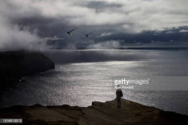 woman on cliff by the sea ireland - landscape scenery stock pictures, royalty-free photos & images