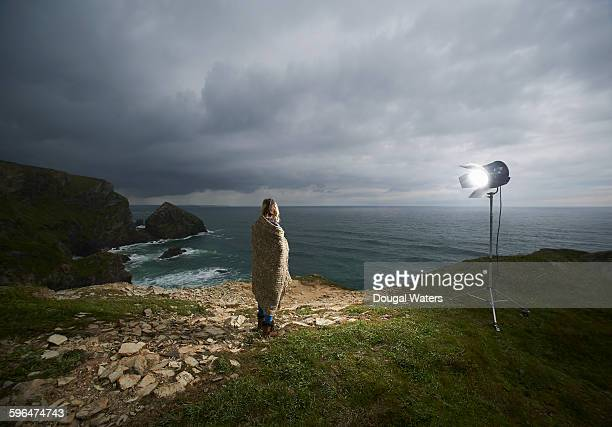 Woman on cliff top lit by spotlight.