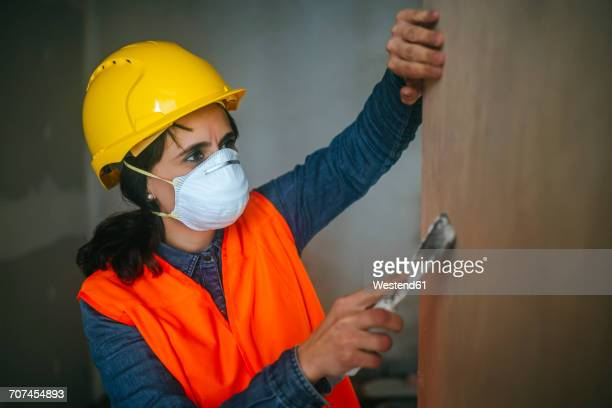 Woman on construction site leveling wall
