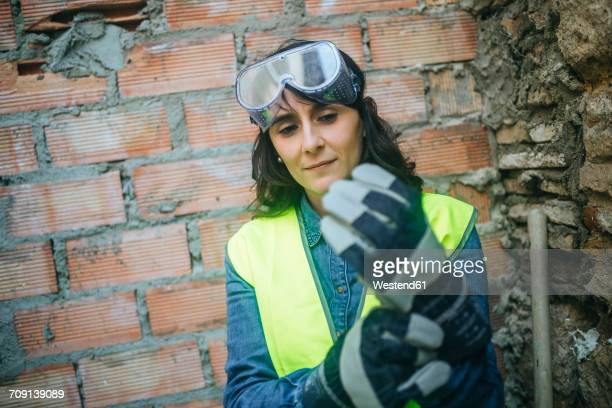 woman on construction site putting on protective gloves - work glove stock photos and pictures