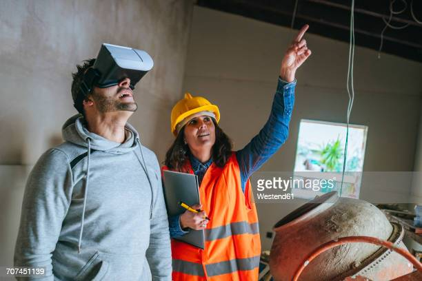 Woman on construction site showing a man with virtual reality glasses the house