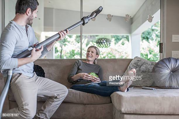 Woman on couch and man pretending playing guitar with vacuum cleaner