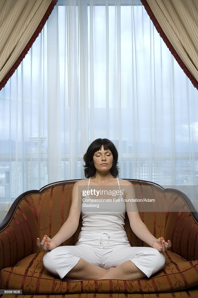 Woman on couch meditating : Stock Photo