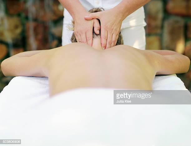 woman on couch receiving massage - massaggio sensuale foto e immagini stock