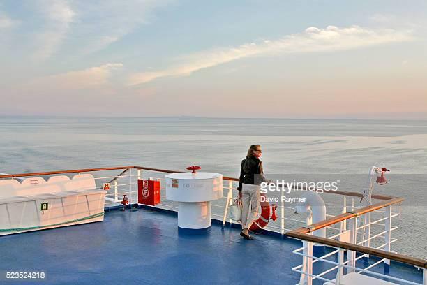 woman on cruise boat looking out to sea - kreuzfahrt stock-fotos und bilder