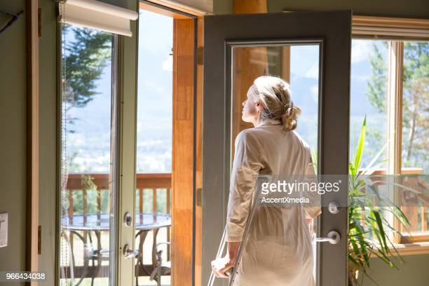 woman on crutches goes to terrace to enjoy fresh air - crutch stock photos and pictures